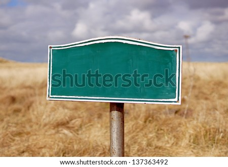 Old sign post, with blank space for own message, against    meadow grass and cloudy sky - stock photo