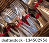 Old silver cutlery tied together with red ribbon in wicker basket. Flea market in Paris. - stock photo