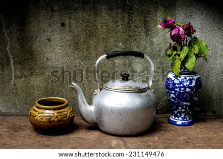 Old silver kettle and vase flower rose  placed on a wooden floor