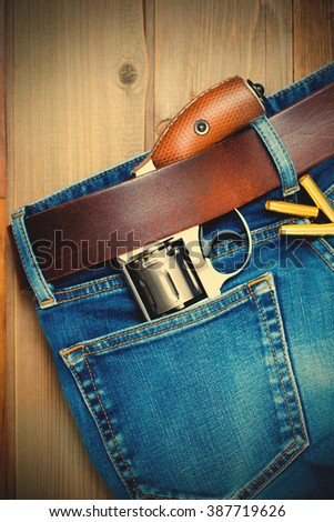 old silver revolver and vintage blue jeans with a leather belt. instagram image filter retro style - stock photo