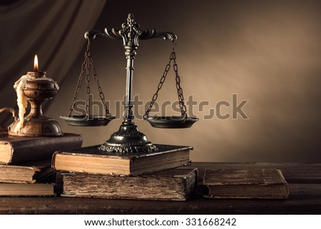 Old silver scale and hardcover books on a wooden table, justice and knowledge concept - stock photo
