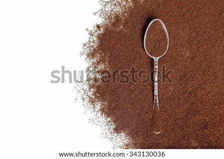 Old silver spoon with ground coffee on a white background. - stock photo