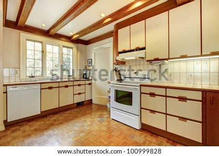 Old simple white and wood kitchen with hardwood floor and white appliances.