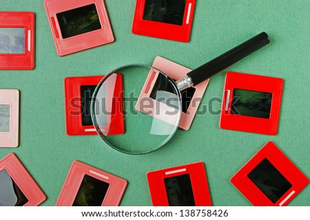 old slides and a magnifying glass on green table - stock photo