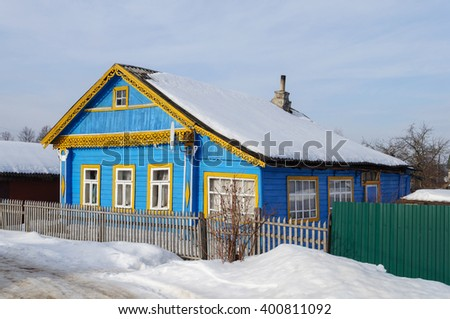 Old small blue wooden house in russian village, sunny winter day - stock photo