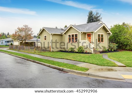 Old small green American home with porch. Green lawn around and driveway