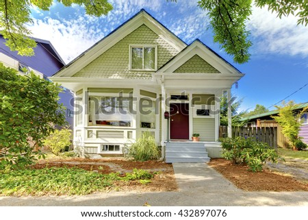 Old small green home with porch and trimmed windows