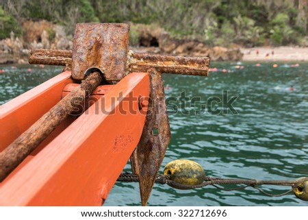 Old small rusty anchor for a small boat  (folding grapnel anchor) - stock photo