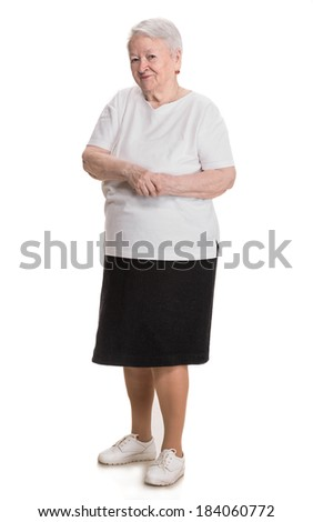 Old smiling woman standing on a white background - stock photo