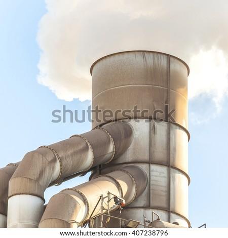 Old smokestack that emits white smoke. - stock photo
