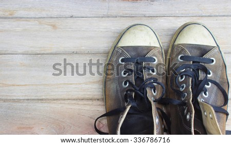 old sneakers on wood - stock photo