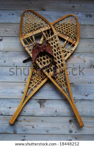 old snowshoes hanging on wall - stock photo