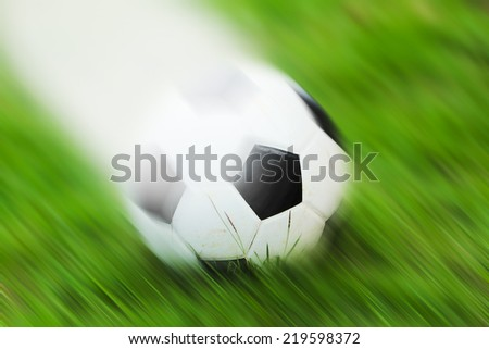 Old soccer ball on grass in the evening. - stock photo