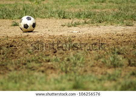 Old Soccer Ball. Poor school soccer field. Charity. - stock photo