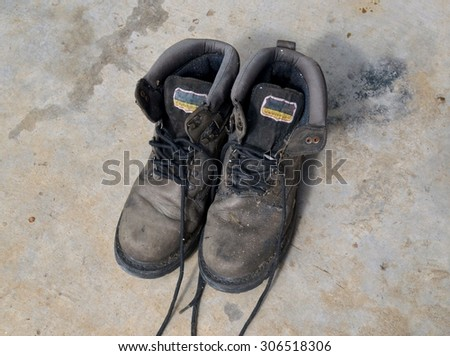 old soldier's boots worn with scratches and untied shoelaces on dark background - stock photo