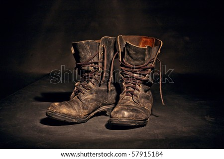 old soldier's boots worn with scratches and untied shoelaces on white background - stock photo