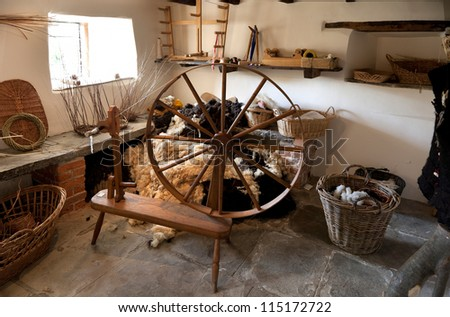 Old spinning wheel with fleece and baskets - stock photo