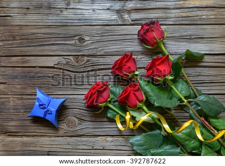 Old splintered wooden background under a bundle of five stemmed roses and star shaped blue box - stock photo