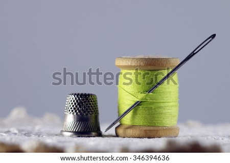Old spool of thread with needle closeup. Tailor's work table. textile or fine cloth making. - stock photo