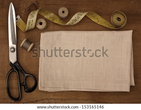 Old spools of thread, fabric, scissors on a wooden background - stock photo
