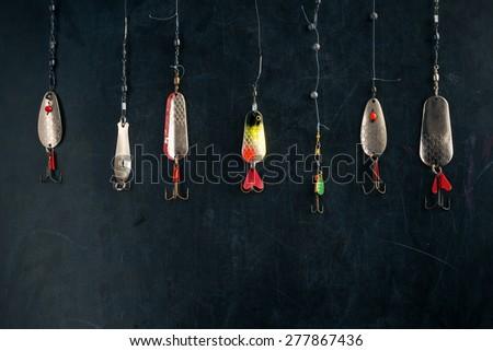 old spoon lures hanging on blackboard - stock photo