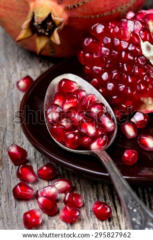old spoon with pomegranate seeds, slices of pomegranate on a wooden background - stock photo