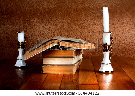 Old stack of books with candlestick and burning candle on the wooden table