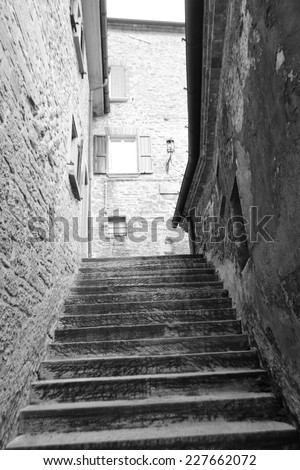 Old stairs on medieval narrow street in San Marino republic, Italy. Black and white. - stock photo
