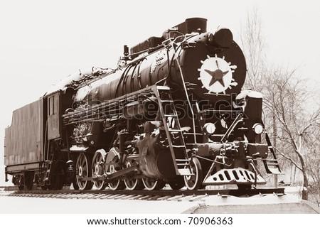old steam locomotive on a pedestal - stock photo