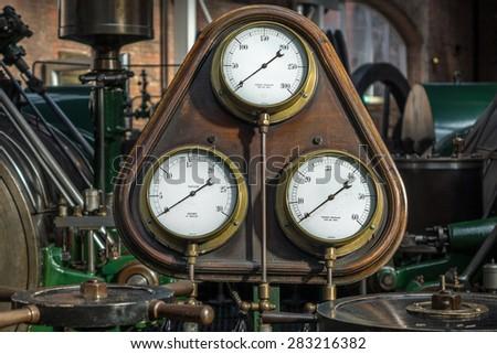 Old steam pressure gauge amid antique steam engines. - stock photo