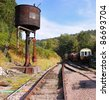 Old steam railway tracks and vintage diesel Locomotives with rusting Water Tower - stock photo