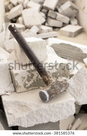 Old steel hammer smashing on broken brick wall - stock photo