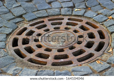 Old steel sewer manhole on the cobblestone road - stock photo