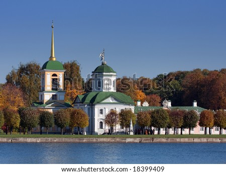 Old steeple on the shore of lake on blue sky background - stock photo