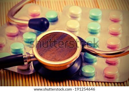 Old stethoscope on background tabs. Vintage style - stock photo