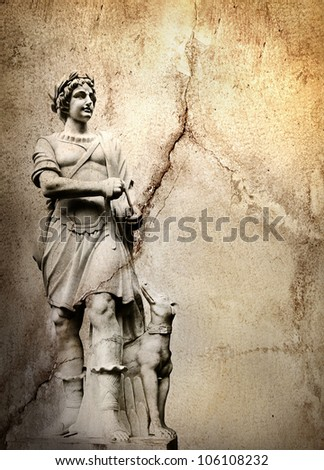 Old stone background with a sculpture man with dog - stock photo
