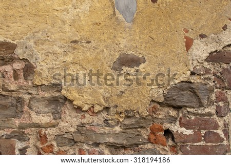 Old stone brick weathered rendered wall dipping mortar - stock photo