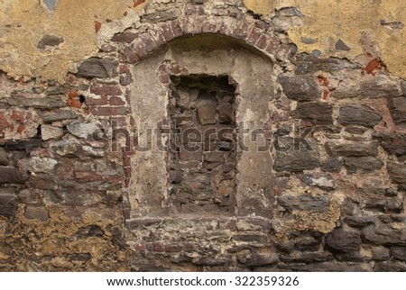 Old stone brick weathered rendered wall with bricked in window portal - stock photo