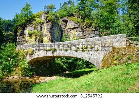 Old stone bridge over a small rivulet in summer season - stock photo