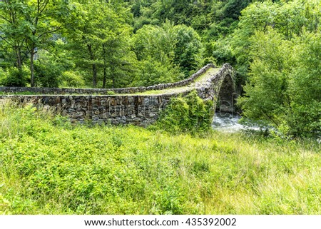 Old Stone bridge over beautiful river in summer - Pyrenees. Andorra la Vella. Andorra.