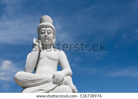 Old stone buddha statue, great for Asia travel and religious themes with beautiful blue sky. - stock photo