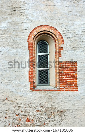 Old stone building wall with nice high gothic window - stock photo