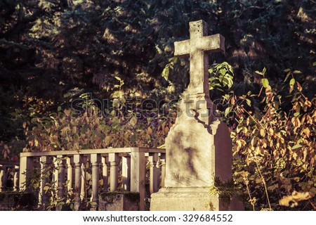 Old stone cross gravestone in dappled evening light with fall leaves. - stock photo