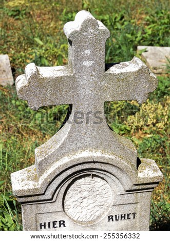 Old stone cross in the cemetery - stock photo