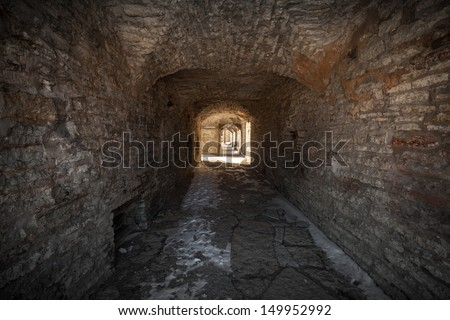Old stone fortress dark stone tunnel perspective with glowing end - stock photo