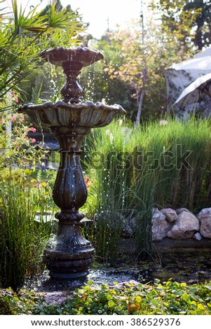 old stone fountain with dripping water in pond vintage garden - stock photo