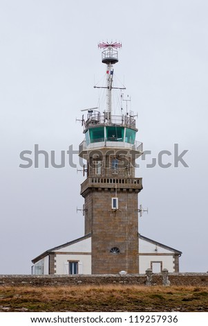 Old stone lighthouse with modern equipment at dull day. Cape Ra, (Pointe du Raz), westernmost France point