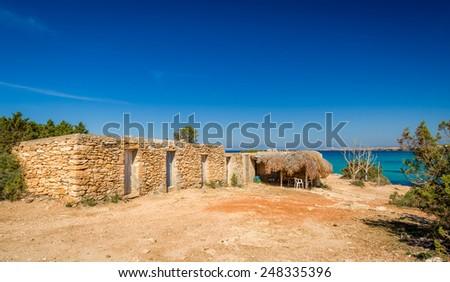 Old stone shanty at Formentera island coast. Cala Saona bay, Baleares, Spain - stock photo