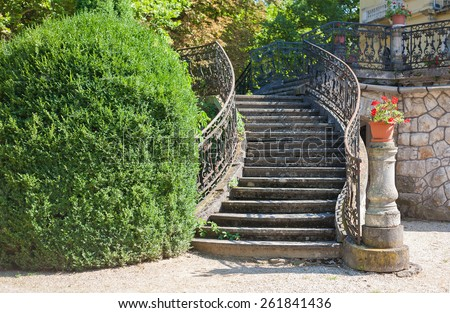 Old stone stairway of a palace with wrought iron banister in a park - stock photo