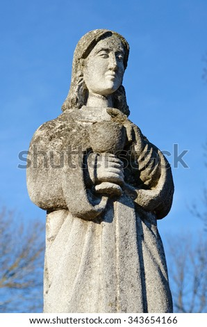 Old stone statue of a woman with a cup for Holy Communion on the headstone in the cemetery in Ukraine - stock photo